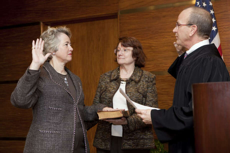 Mayor Annise Parker gets sworn in with her grandparents' Bible, shown being held by Parker's partner, Kathy Hubbard, on Saturday. State District Judge Steven Kirkland administers the oath. Photo: Jenny Antill