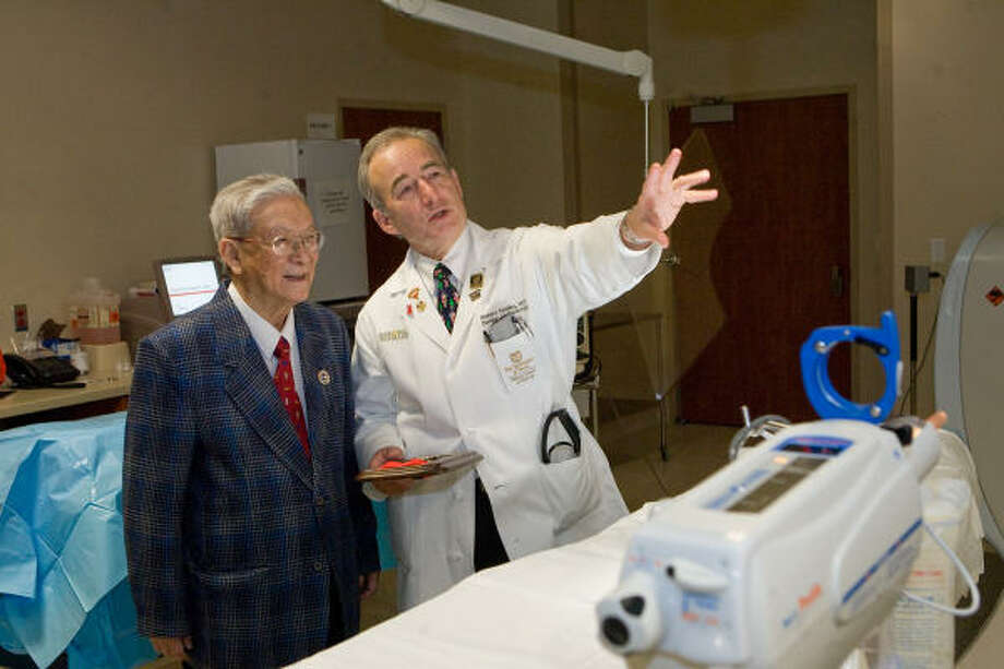 "A LOOK AROUND: Senior table tennis champion Rushan Gao, left, visits a cardiac cath lab at Memorial Hermann Medical Center hospital with Dr. Richard Smalling, of the Memorial Hermann Cardiovascular Institute. Smalling was one of the two doctors Gao calls his ""Lifesavers."" Before entering the Huntsman World Senior Games, Gao dedicated any medals he might win to his them. He recently delivered on that promise by giving away three gold medals. Photo: R. Clayton McKee, For The Chronicle"
