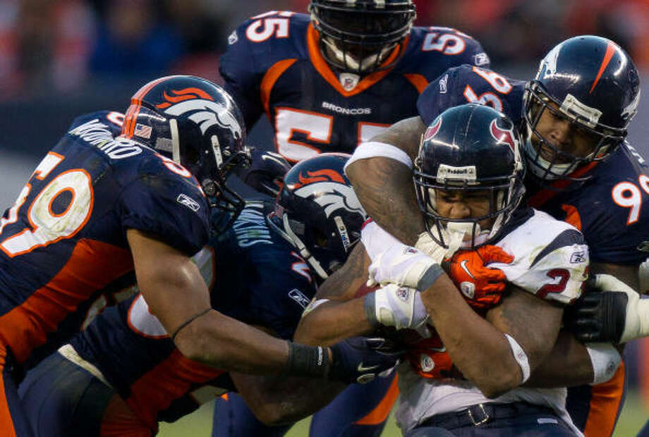 Texans running back Arian Foster (23) is wrapped up by a herd of Broncos defenders Sunday. Foster carried the ball 19 times  and picked up 91 yards to lead both teams in that department. Photo: Smiley N. Pool, Chronicle
