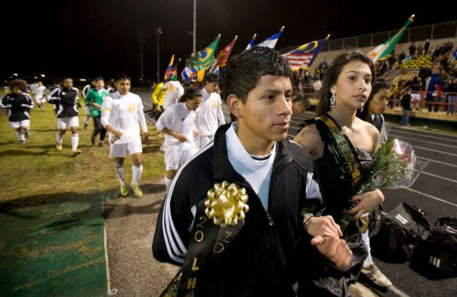 Lee High School varsity soccer player Gerardo Blanco, the homecoming king, escorts homecoming queen Cynthia Cortez at halftime of Lee's game at Butler Stadium on Friday. Photo: Nick De La Torre, Chronicle