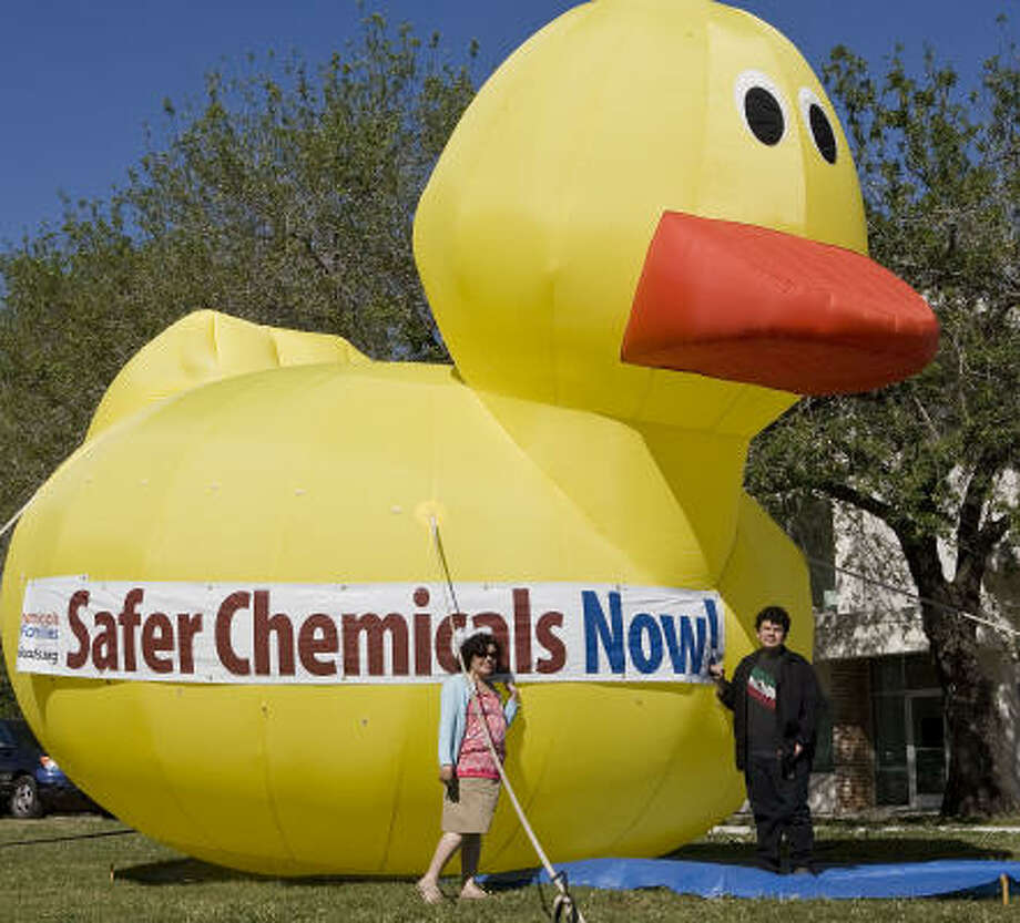 Rosalia Guerrero-Luera  and her son Cosme Castillo stand in front of a 20-foot inflatable Betty the Be Safe Rubber Duck during a test inflation of the duck for Air Alliance Houston. Photo: James Nielsen, Chronicle