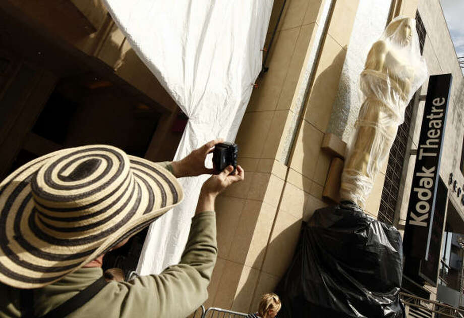 A tourist takes a photo of an Oscar statue outside the Kodak Theatre in Los Angeles, where the 82nd Academy Awards ceremony will be held on Sunday. Photo: Matt Sayles, AP