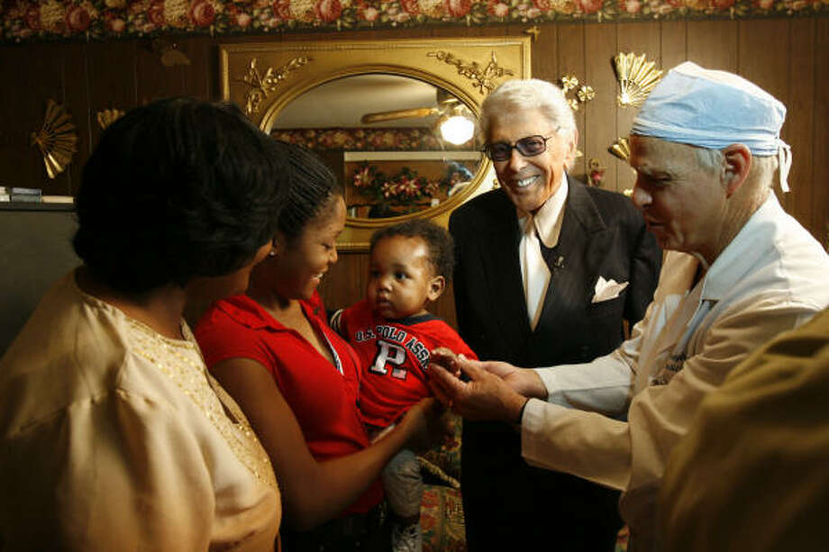 Plastic surgeon Dr. Joseph Agris, at right, and the late Marvin Zindler teamed up to help children throughout the world. In this 2006 photograph, they are shown with some beneficiaries of their charity work: from left, Fonda Burch, her daughter Ronesha Burch, holding son Jeremiah. Photo: Billy Smith II, Chronicle