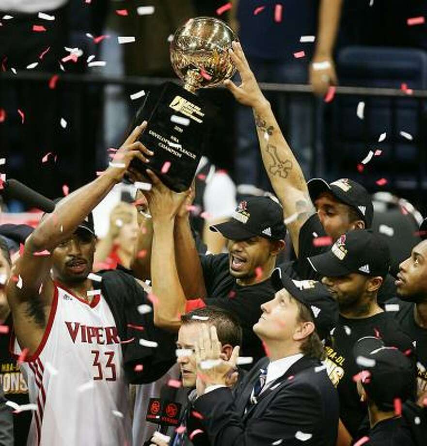 Mike Harris along with head coach Chris Finch and teammates hoist the  NBADL League trophy after defeating the Tulsa 66'ers in Game 2 on Tuesday. Photo: DELCIA LOPEZ, AP