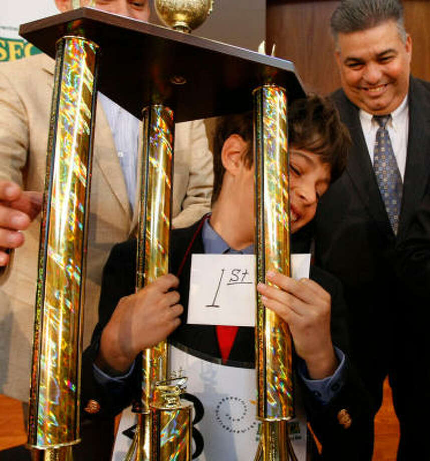 Jacob Roffwarg, 10, of HISD's Mark Twain Elementary, struggles with his trophy Saturday after winning the annual Maseca Bilingual Spelling Bee at Houston Baptist University. Photo: Julio Cortez, Chronicle