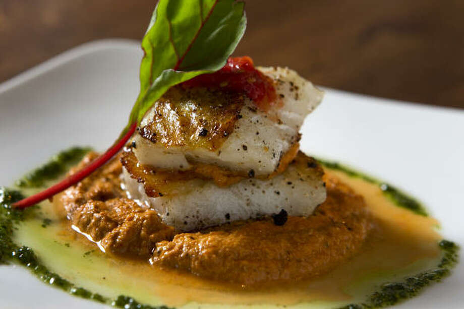 The seared cod is served in a luxurious pool of red-pepper romesco sauce with ground almonds, a garlicky fresh-tomato coulis and bright herbal dots of parsley oil. Photo: Brett Coomer :, Chronicle