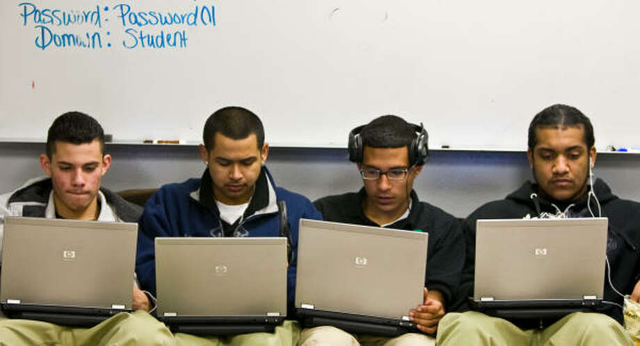 From left, Jairo Ramirez, 16, Yobanix Funes, 18, Adolfo Serrano, 18, and Milton Valencia, 17, fill a couch at Sharpstown High School on Friday and use laptops to work on recovering credits for classes they failed. Photo: Nick De La Torre, Chronicle
