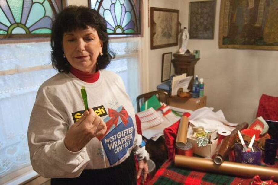 """Sylvia Houston shows her newest """"secret weapon"""" in the competitive world of wrapping presents, a wrapping paper cutter. R. Clayton McKee: For The Chronicle."""