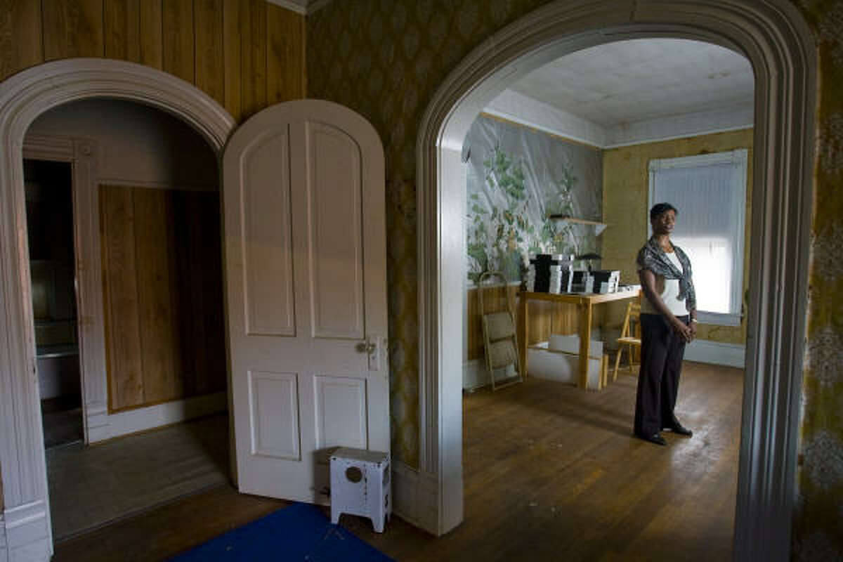 Debra Blacklock-Sloan, historical researcher for the R.B.H. Yates Museum, surveys a room in the Rev. Ned P. Pullum House. When a fundraising campaign is complete, the home is to be restored and renamed the Pullum Health and Business Museum .
