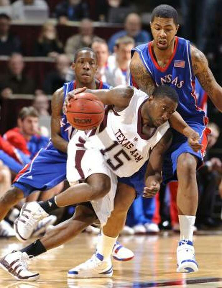 Texas A&M's Donald Sloan tries to get around a pair of Jayhawks defenders. Photo: Dave Einsel, AP