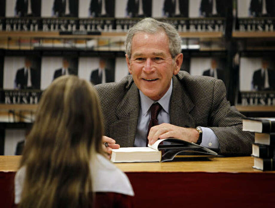 Former President George W. Bush talks with 8-year-old Whitney Grace Dodson, as he signs copies of his book, Decision Points, Tuesday at a store near his Dallas home. Photo: G.J. McCARTHY,  THE DALLAS MORNING NEWS