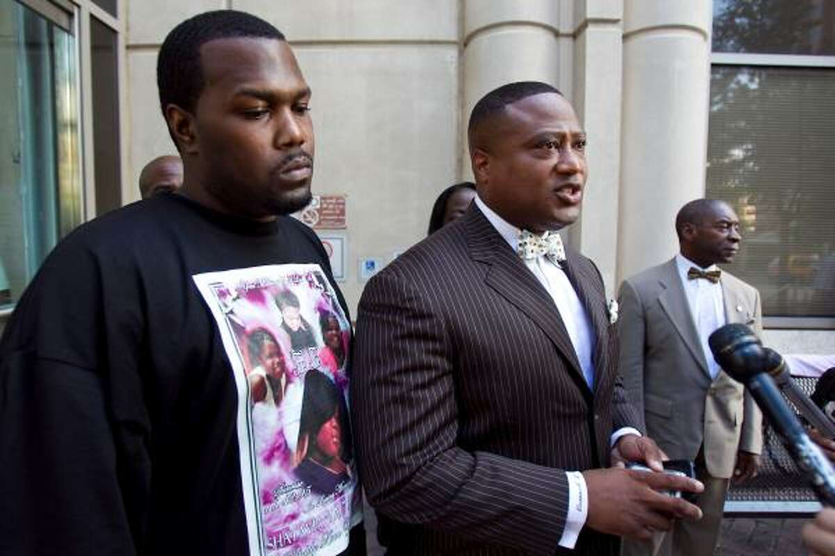 Community activist Quanell X , center, calls immigration laws toothless as he talks to the media Friday outside the Harris County Justice Center. Police have said a suspect in the death of Shatavia Anderson, the 14-year-old daughter of Leroy Anderson, left, had been deported twice.