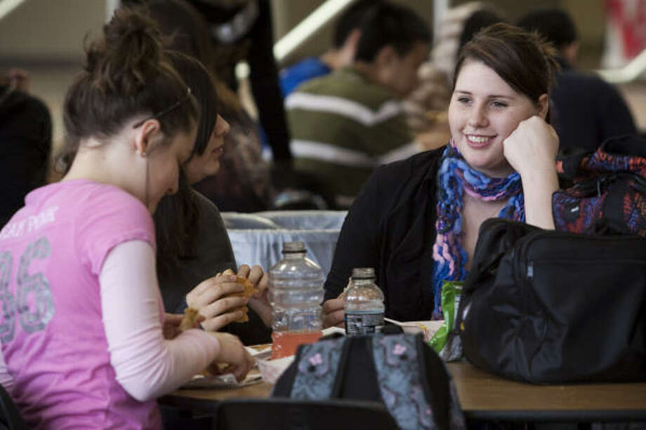 Carly Davis, right, is joined by friends Felicia Chandler, left, and Destiny Juarez during lunch Friday at Foster High School in Richmond. It was Carly's last day attending classes. She suffers from terminal cancer, and she and her mother are moving to Utah. Photo: Eric Kayne, For The Chronicle