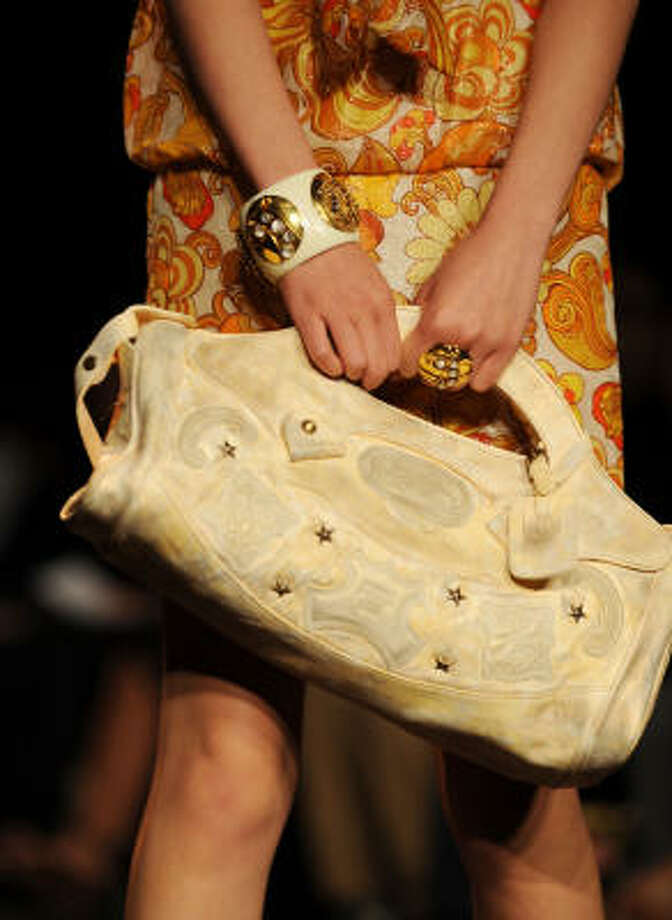 A white handbag and simple gold jewelry complement Anna Sui's runway collection. Photo: STAN HONDA, AFP/Getty Images