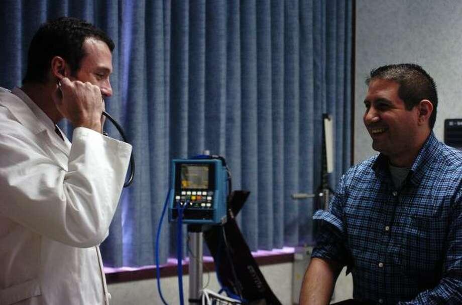 Guiar a los pacientes: es lo que hace el doctor García, izq., mientras chequea a Tres Barrera. Photo: Shaminder Dulai, Para La Voz