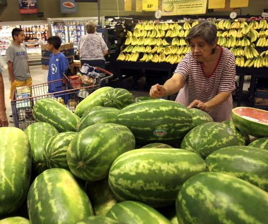 Irene Fernandez knocks on watermelons at an H-E-B in San Antonio to see which one she wants to purchase. An oversupply of the fruit this summer means prices could be down by 25 percent from last year. Photo: Helen L.. Montoya, San Antonio Express-News