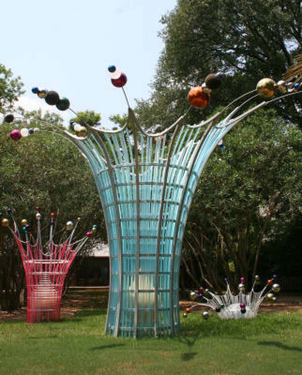 The Dennis Oppenheim creation includes three sculptures (from left) Splash (Tall Pink), Splash and Splash (Low White). The sculptures are made with colored stainless-steel globes, powder-coated steel, stainless-steel ties and acrylic.