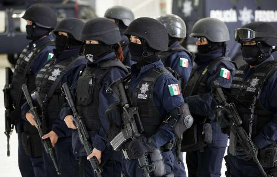 Federal police officers stand in formation in June while drug-dealing suspects are presented to the media in Mexico City. The officers' faces are covered to protect their identities. Photo: Eduardo Verdugo, Associated Press
