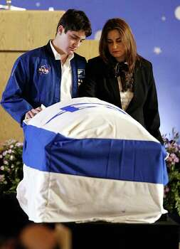 FILE - In this Feb. 10, 2003 file photo, Rona Ramon, widow, right, and Assaf Ramon, left, eldest son of Israel's first astronaut Ilan Ramon, pay their respects beside his coffin during a memorial service at Ben Gurion International Airport outside Tel Aviv. Ramon, a 48 year old air force colonel, died with six other astronauts aboard NASA's Columbia space shuttle, which was destroyed as it came through the Earth's atmosphere on Feb. 1, 2003. Assaf wears his father's NASA flight jacket. Assaf Ramon grew up to become an Israeli Air Force pilot like his father. He was killed when his fighter jet crashed during a training exercise in 2009. He was 21. Photo: AP