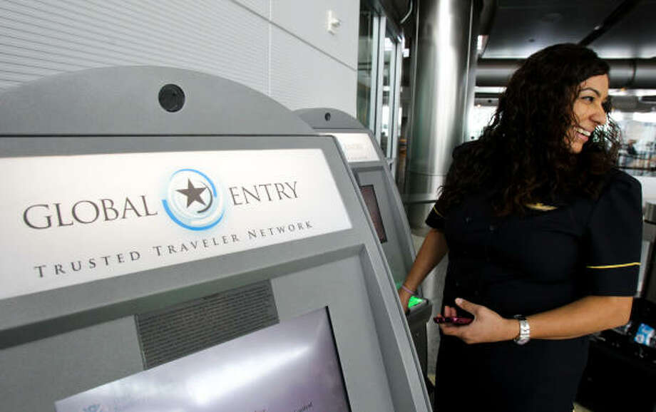 Looking over at a friend who had to get in the queue, Lizzethe Escoto of Continental Airlines uses a Global Entry kiosk to enter the country last week at Bush Intercontinental Airport. Photo: Nick De La Torre :, Chronicle