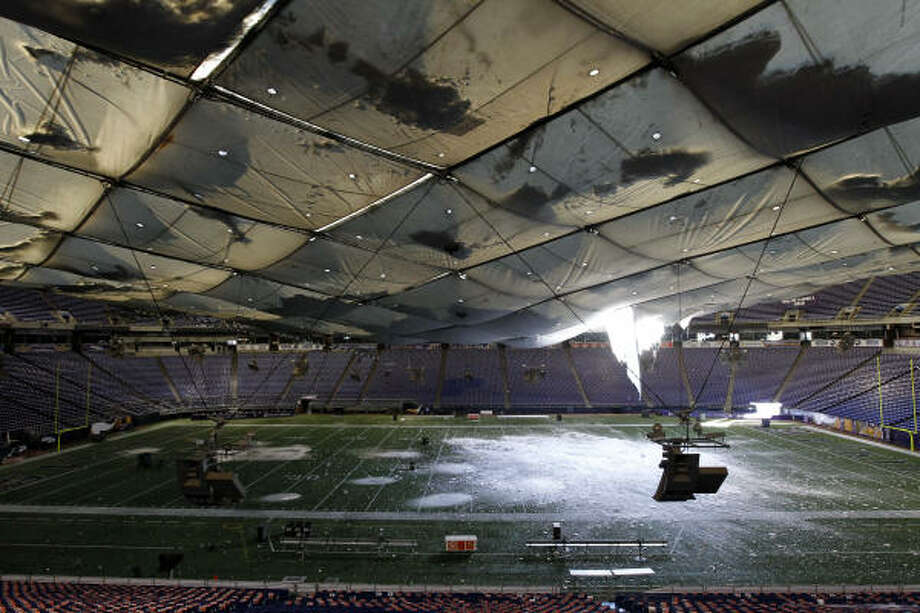 Snow falls unto the field from a hole in the collapsed roof of the Metrodome in Minneapolis on Sunday. Photo: Ann Heisenfelt, AP
