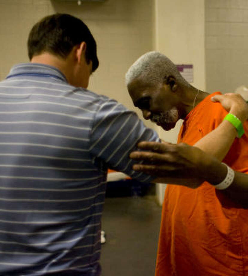 Bill Deloache Jr., one of some 300 Christian volunteers with the Pro-Claim prison ministry, prays with Donald Odom, 55, an inmate at the Harris County Jail on 1200 Baker in Houston. Photo: Johnny Hanson, Chronicle
