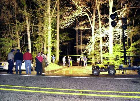 Authorities gather near the site of a helicopter crash that killed two people and injured the other three aboard Thursday, March 27, 2003, in the Angelina National Forest near Broaddus, Texas. The U.S. Forest Service helicopter was searching for space shuttle Columbia debris. Photo: JOEL ANDREWS, AP / THE LUFKIN DAILY NEWS