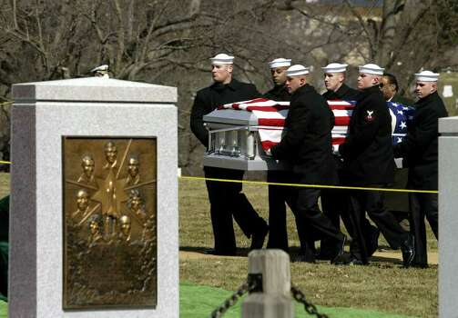 The flag-draped casket of space shuttle Columbia astronaut Laurel Clark is carried by an honor guard past the gravestone of the space shuttle Challenger crew at Arlington National Cemetery in Arlington, Va., Monday, March 10, 2003. Clark and six fellow astronauts perished aboard the space shuttle Columbia when it disintegrated in flames over Texas on Saturday, Feb. 1, 2003 minutes before it was to land in Florida. Photo: J. SCOTT APPLEWHITE, AP / AP