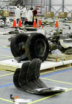 The tires of the front landing gear of the space shuttle Columbia and other pieces of space shuttle debris lie in this hangar at the Kennedy Space Center in Cape Canaveral, Fla. Wednesday March 5, 2003. On the bottom of the photo is wreckage containing tiles from the front of Columbia. Photo: JOE SKIPPER, AP / POOL REUTERS