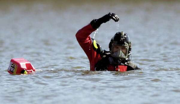 Environmental Protection Agency diver Brian Holderness, beside a marker, left,  signals to the boat while searching for debris from space shuttle Columbia in Toledo Bend Reservoir in Six Mile, Texas Tuesday, Feb. 18, 2003. Photo: DAVID J. PHILLIP, AP / AP