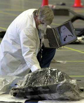 A member of the Columbia investigating team holds a computer with the foward section of a shuttle displayed as he checks through Columbia wreckage in a hangar at the Kennedy Space Center in Cape Canaveral, Fla. Friday Feb. 14, 2003. Photo: PETER COSGROVE, AP / AP