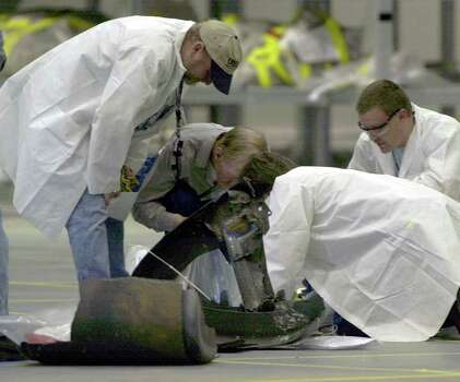 Members of the space shuttle Columbia accident investigation team check out a piece of wreckage in a hangar at the Kennedy Space Center in Cape Canaveral, Fla. Friday Feb. 14, 2003. Wreckage from Texas and Louisiana is being shipped to this facility. Photo: PETER COSGROVE, AP / AP
