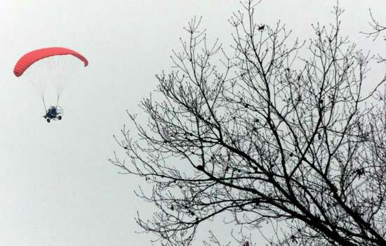 A searcher uses a powered parachute to fly above  trees to look for space shuttle Columbia debris near Melrose, Texas, Sunday, Feb. 9, 2003. Three large pieces of debris from the space shuttle Columbia, including one that appears to be a hatch door, were located Sunday, officials said. Photo: DONNA MCWILLIAM, AP / AP