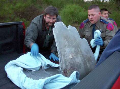 ** FILE ** Paul Miller, left, with the help of an unidentified Texas Department of Public Safety officer,  load debris  believed to be from the shuttle Columbia into a truck near Nacogdoches, Texas, Tuesday, Feb. 4, 2003. Miller says state troopers on Thursday, Feb. 6, 2003, stormed his aircraft simulator company in Azle, Texas,  accusing him of hoarding debris he'd found two days earlier. But the items  3-by-3-foot wing part, circuit board and data collection device - were later found at the Nacogdoches Airport, where he'd turned them in before returning home. Photo: JIM WALLS, AP / JIM WALLS