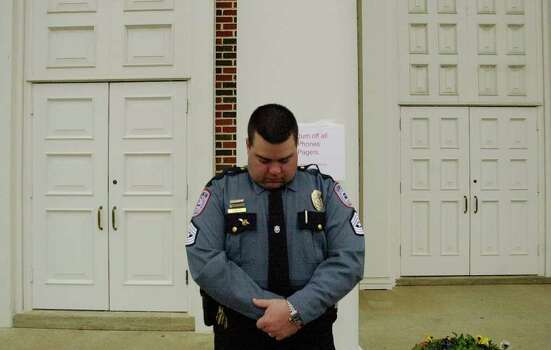 STATE -  Lufkin Police Sgt. Ronny LaRue bows his head in remembrance at the exact hour one week after Space Shuttle Columbia was to have landed in Florida. LaRue was standing guard at the door to a memorial service at the First Baptist Church in Lufkin on Saturday, Feb. 8, 2003.  The Space Shuttle Columbia broke apart over East Texas upon re-entry on Feb. 1, 2003. BILLY CALZADA / STAFF Photo: BILLY CALZADA, SAN ANTONIO EXPRESS-NEWS / SAN ANTONIO EXPRESS-NEWS