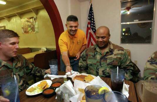 STATE -  National Guardsmen Robert Sheffield, left, and Gary Hightower are served by Roberto Covarrubias at El Giro Mexican Restaurant in Hemphill, Texas, on Friday, Feb. 7, 2003.  The guardsmen have been spending their days searching for shuttle debris. The Space Shuttle Columbia broke apart over East Texas upon re-entry on Feb. 1. BILLY CALZADA / STAFF Photo: BILLY CALZADA, SAN ANTONIO EXPRESS-NEWS / SAN ANTONIO EXPRESS-NEWS