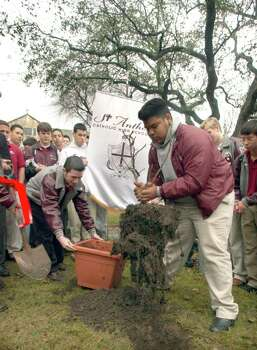 Metro daily - Adrian Zapata, right, plants a fig tree as students at St. Anthony's Catholic High School gather around.  The tree planting was in honor of the space shuttle Columbia astronauts, Thursday, Feb. 6, 2003, in front of the campus chapel.  photo bob Owen Photo: BOB OWEN, SAN ANTONIO EXPRESS-NEWS / SAN ANTONIO EXPRESS-NEWS