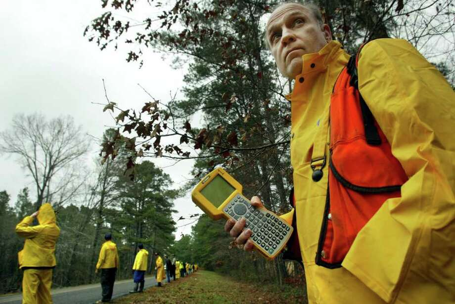 John Guedry with the U.S. Forest Service, right, carries a GPS plotter Monday, Feb. 3, 2003, as volunteers set out to search the forest near Hemphill, Texas. Photo: MICHAEL MULVEY, AP / DALLAS MORNING NEWS