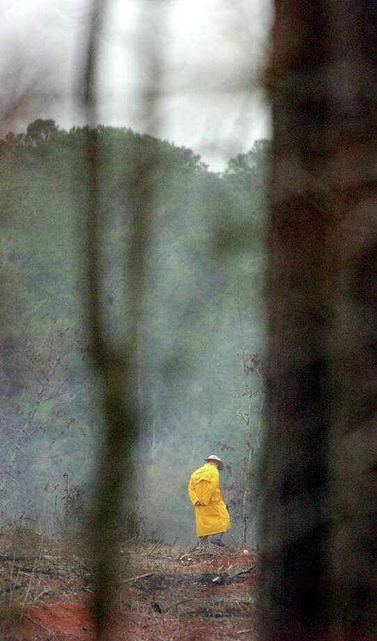 A searcher looks through the woods near San Augustine for remains of the space shuttle on Monday, Feb. 3, 2003. Space Shuttle Columbia broke apart over Texas upon re-entry on Saturday morning. Photo: BILLY CALZADA, SAN ANTONIO EXPRESS-NEWS / SAN ANTONIO EXPRESS-NEWS