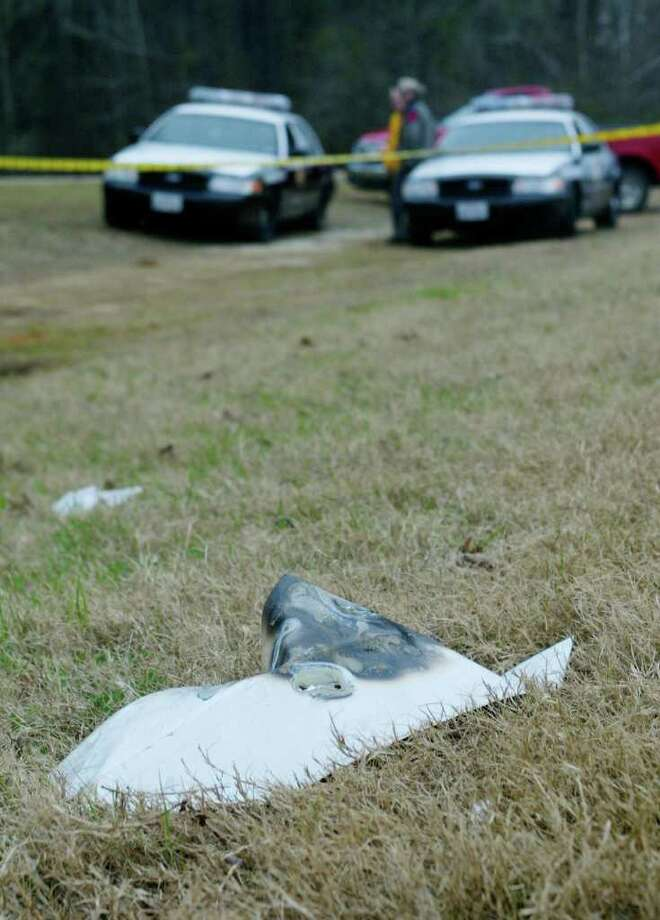 State troopers guard a piece of debris from the space shuttle Columbia in Etoile, Texas, Sunday, Feb. 3, 2003. Authorities used horses and satellite gear Sunday to search for more scorched pieces of space shuttle Columbia across the Texas and Louisiana countryside, as NASA moved ahead with its investigation and the seven astronauts were mourned at church services around the nation. Photo: SUE OGROCKI, AP / AP