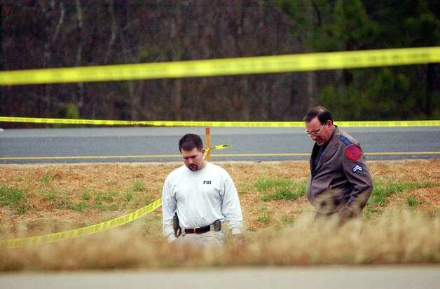 An FBI agent and a Texas Department of Public Safety officer look over a 4-foot by 6-foot piece of the Space Shuttle Columbia that lies in the median along State Highway 155 north of Palastine, Texas  on Sunday, Feb. 2, 2003. The space shuttle blew up over North Texas and pieces of the wreckage are scattered over East Texas and Louisiana.  Photo: JERRY LARA, SAN ANTONIO EXPRESS-NEWS / SAN ANTONIO EXPRESS-NEWS