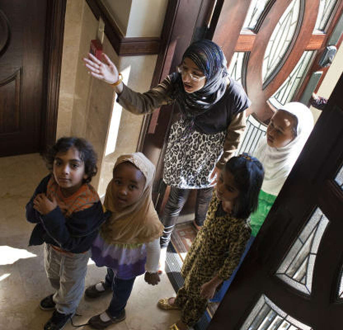 Almira Bhogwani, 16, leads small children for a restroom break at Sugar Land's Maryam Masjid, a mosque that was completed three months ago.
