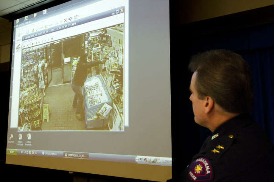 Pasadena Police spokesman Bud Corbett watches video of the deadly armed robbery during a news conference on  Saturday. Photo: Brett Coomer, Chronicle
