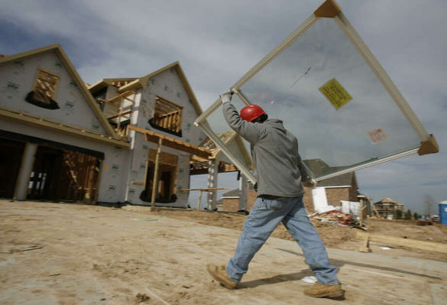Roberto Portillo, who works for Goosneck, a delivery company, carries windows Monday to a home being built at Park Place in Cinco Ranch. Photo: Julio Cortez, Chronicle
