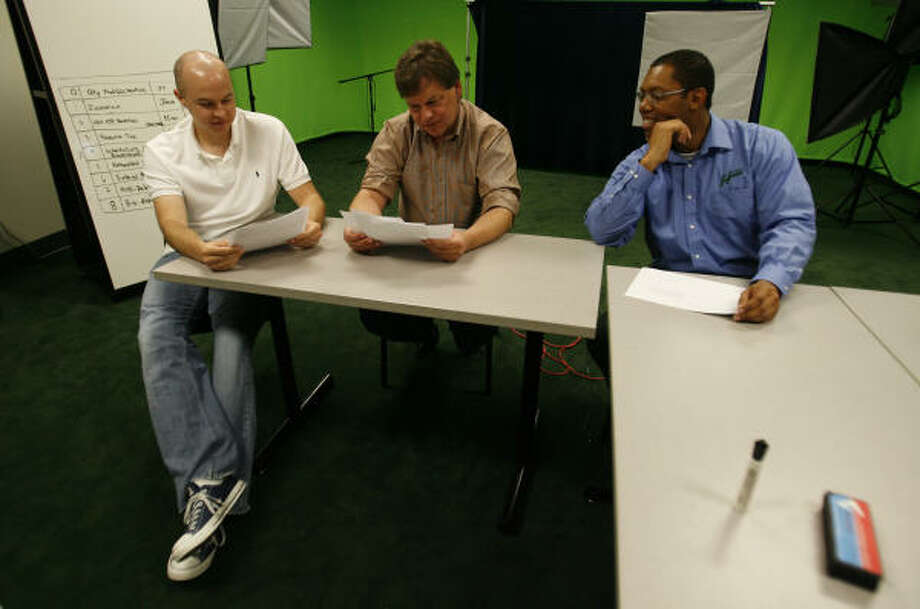 "Software developers Brad Schaefer, left, and John Ehlinger, middle, study their scripts for a humorous video as Sebabi Leballo, the organizational development manager at HCSS, looks on in the ""green screen"" room of the construction software company. Photo: Karen Warren :, Chronicle"