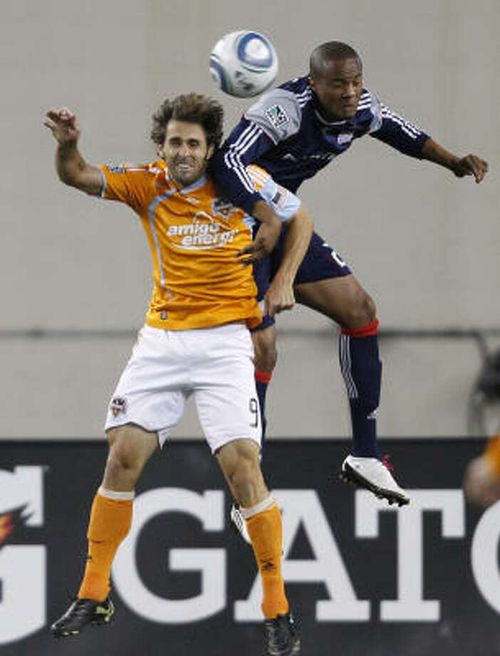 Dynamo midfielder Brian Mullan and Revolution defender Darrius Barnes battle for the ball. Photo: Michael Dwyer, AP