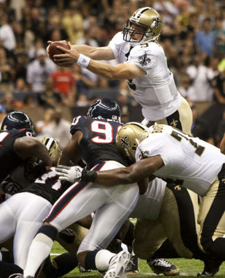 Saints quarterback Drew Brees leaps over the goal line to score a 1-yard touchdown in the first quarter. Photo: Brett Coomer, Chronicle