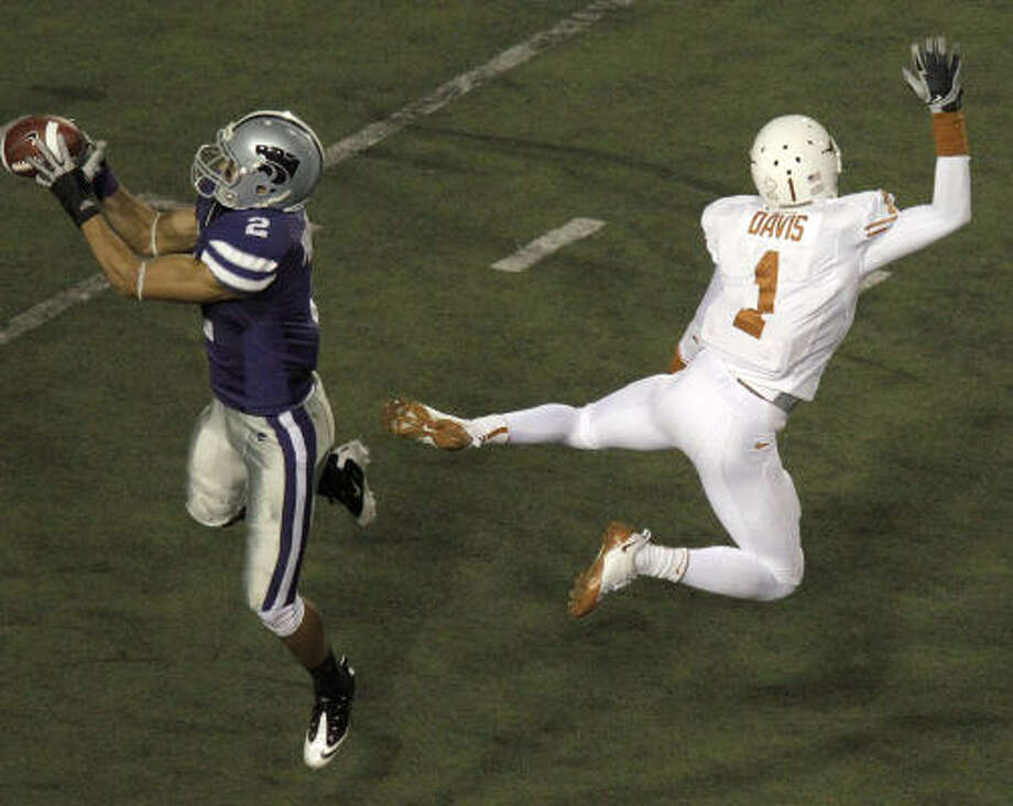 Kansas State cornerback Tysyn Hartman, left, intercepts a pass intended for Texas wide receiver Mike Davis during the second quarter. Photo: Charlie Riedel, AP