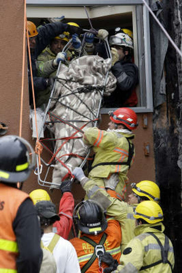 Rescue workers lower the body of an earthquake victim from a collapsed building in Concepcion, Chile, on Sunday. Photo: Aliosha Marquez, AP