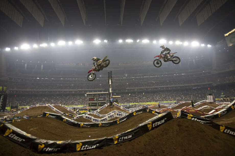 Riders including Michael Willard, right, soar during Saturday's AMA Supercross 250 East race at Reliant Stadium. Christophe Pourcel won the 250 main event and secured the season title. Photo: Nathan Lindstrom, For The Chronicle